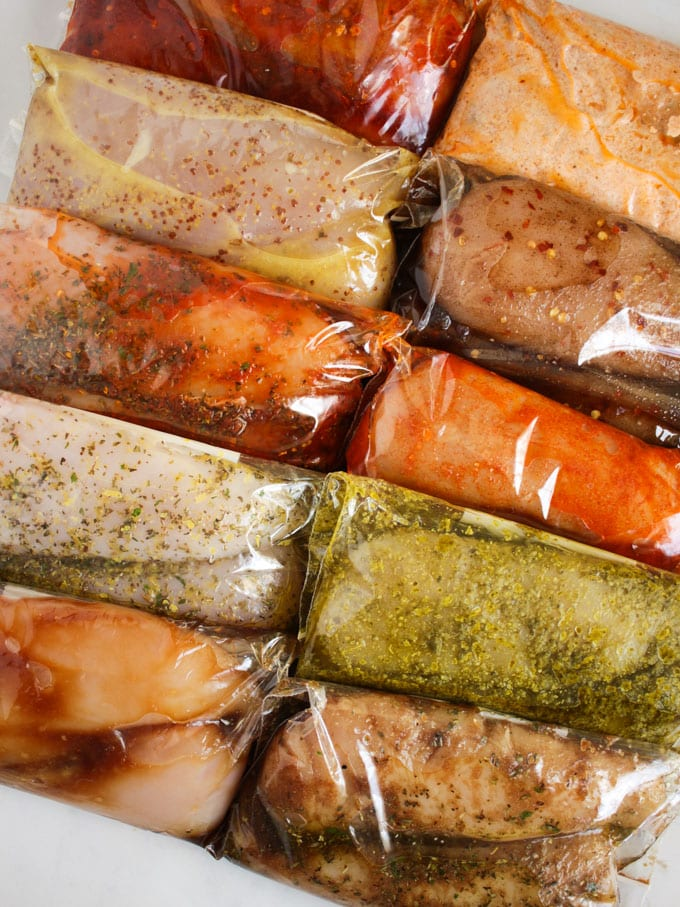 Chicken breasts in different marinades in plastic bags