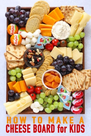 Cheese platter for kids with grapes, crackers, nuts and tomatoes on a board