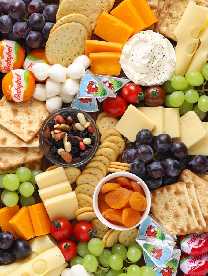 Cheese platter for kids with grapes, crackers, nuts and tomatoes