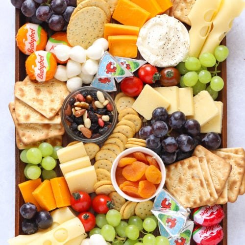 Cheese platter board for kids with child friendly snacks and fruit