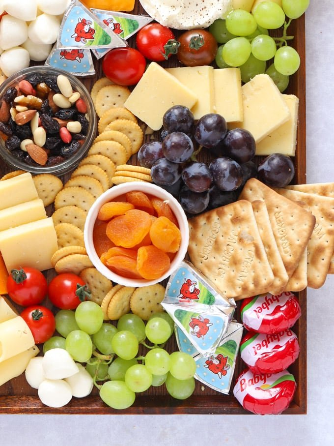 Apricots, grapes and cheeses with crackers on a board