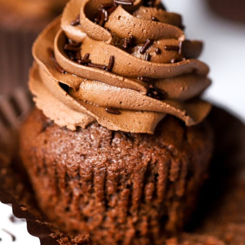 Quick and easy chocolate cupcake with chocolate buttercream icing swirl on top and sprinkles