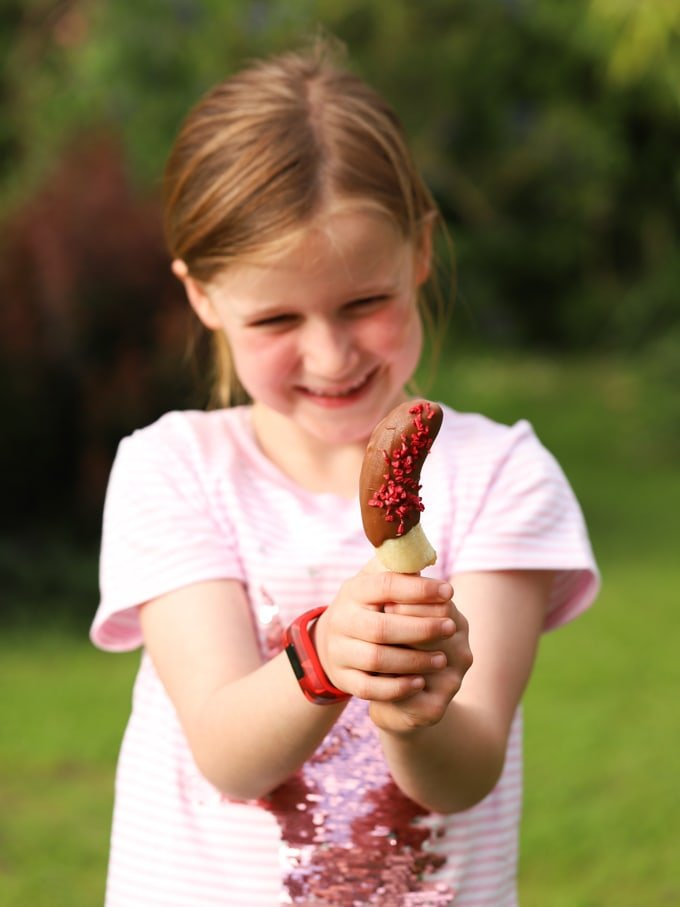 Girl holding homemade lolly with sprinkles and garden in background
