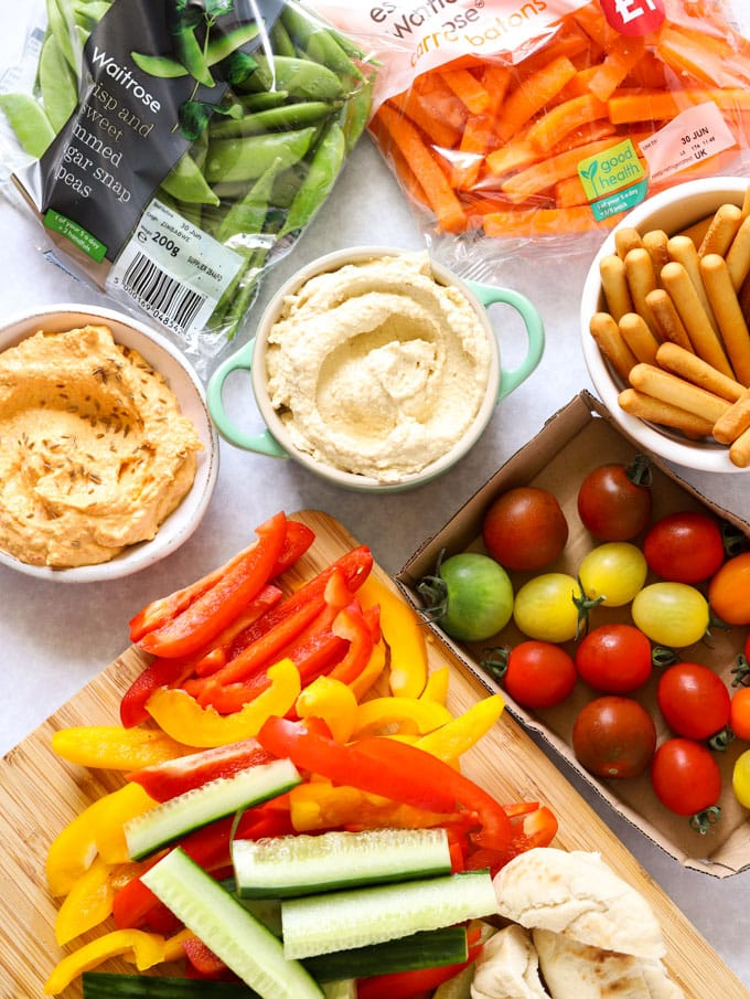 houmous and crudités including tomatoes, sugar snap peas and peppers