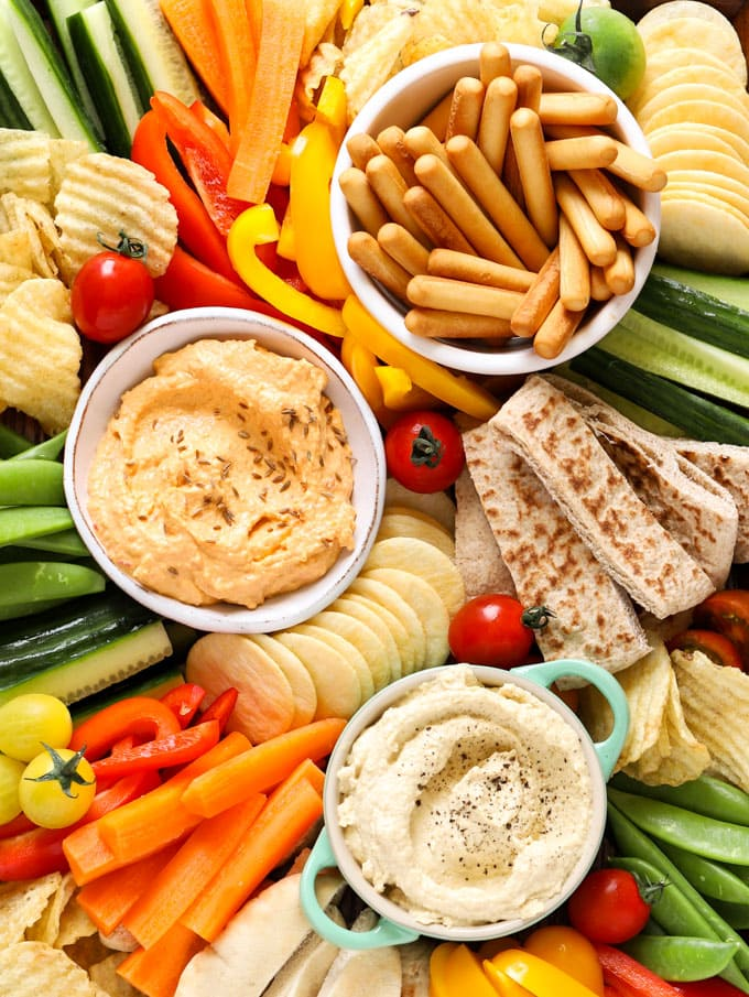 Hummus platter with breadsticks, dips, crisps, cucumber, tomatoes, carrots and crisps