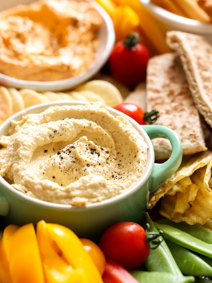 Close up of houmous with crisps and peppers and pitas