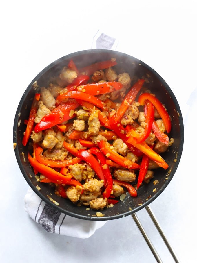 Peppers, sausage and onions frying in a frying pan