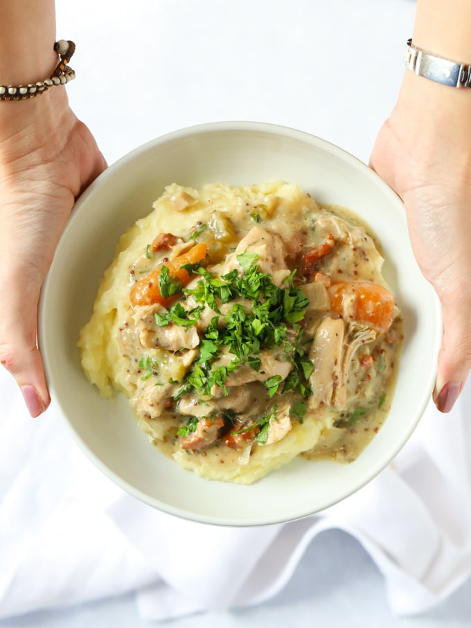 Hands holding a bowl of chicken stew and mashed potatoes