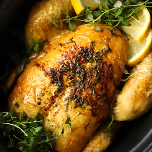 Slow cooker whole roast chicken in a crock pot pan with lemon and herbs