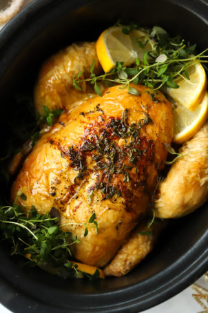 Slow cooker whole chicken in a crock pot pan with roast lemon and herbs