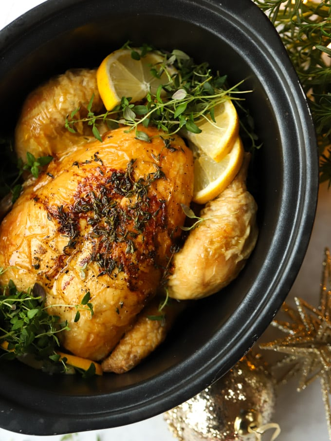 Slow cooker whole chicken in a crock pot pan with lemon and herbs