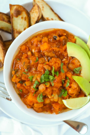 Vegetarian chilli made with butternut squash and chipotle served with potato wedges, avocado and lime