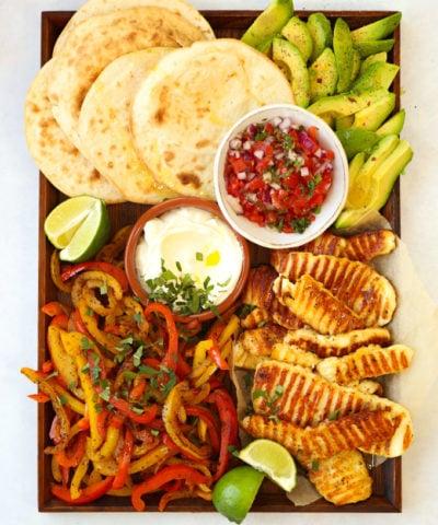 Halloumi fajitas recipe on a board with tortilla wraps avocado and salsa