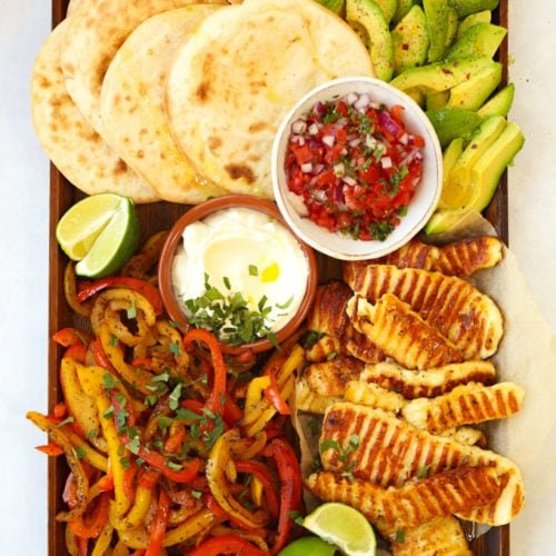 Halloumi fajitas recipe on a board with tortilla wraps avocado and salsa