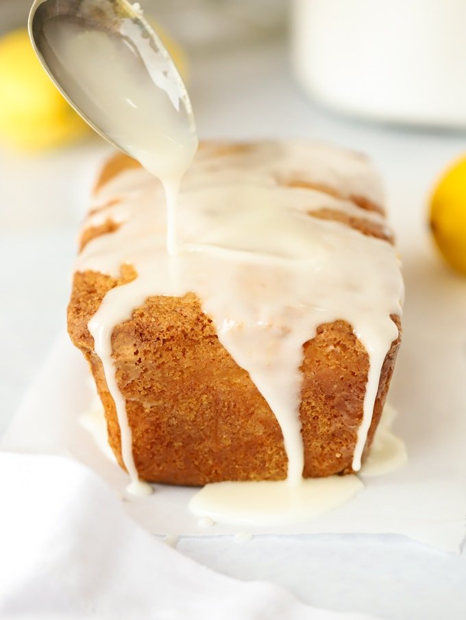 Lemon drizzle cake with drizzle icing pouring over the top of it