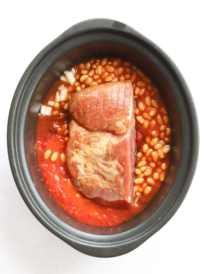 Uncooked ham in slow cooker with beans