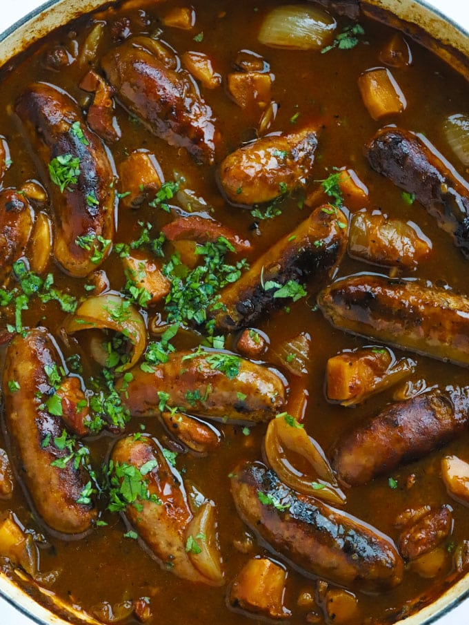 Sausage casserole recipe with apples, cider and bacon sprinkled with herbs