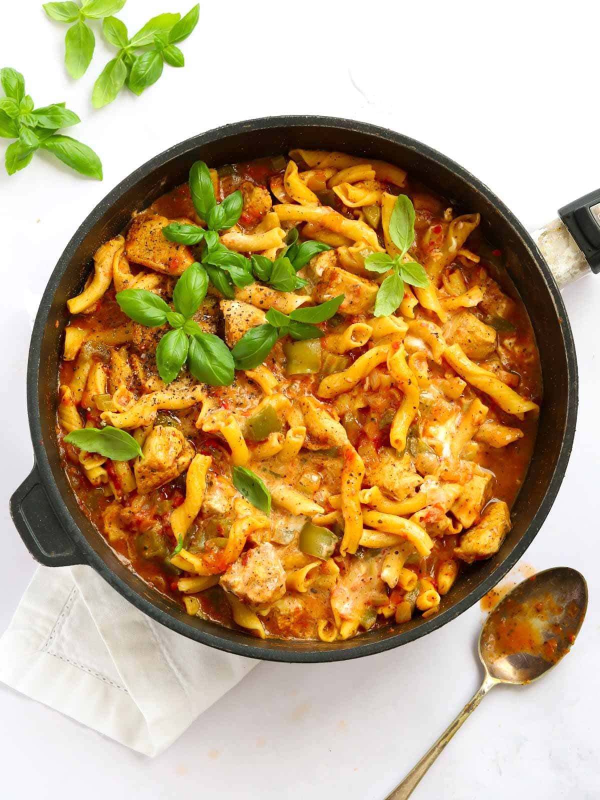 Pan of pasta with tomato and chicken sauce with green peppers and onions and basil
